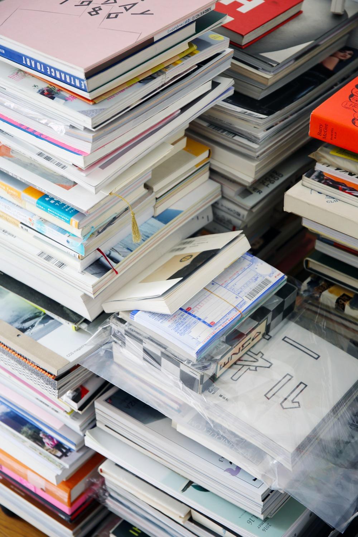机の横に山積みにされた古本。ネットに登録したものと、これから登録するもので山を分けているそう。