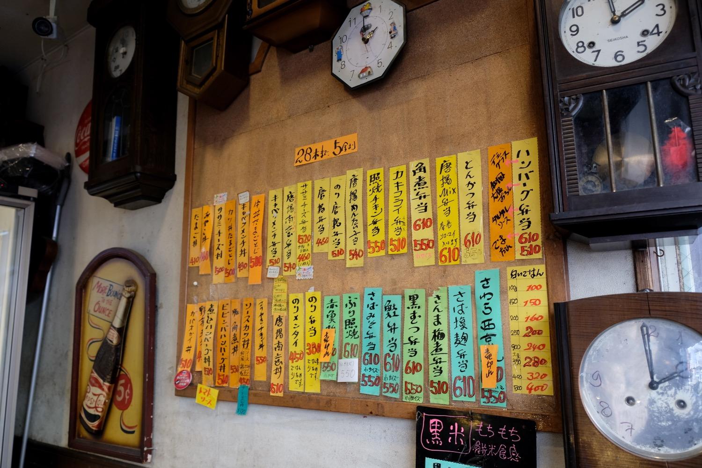 吉祥寺末広通りにあるお惣菜屋さん「二丁目SOZAI」。種類豊富なおにぎりやお弁当が地元のひとに愛される名店。店内の壁面にはなぜか壁掛け時計がずらり。