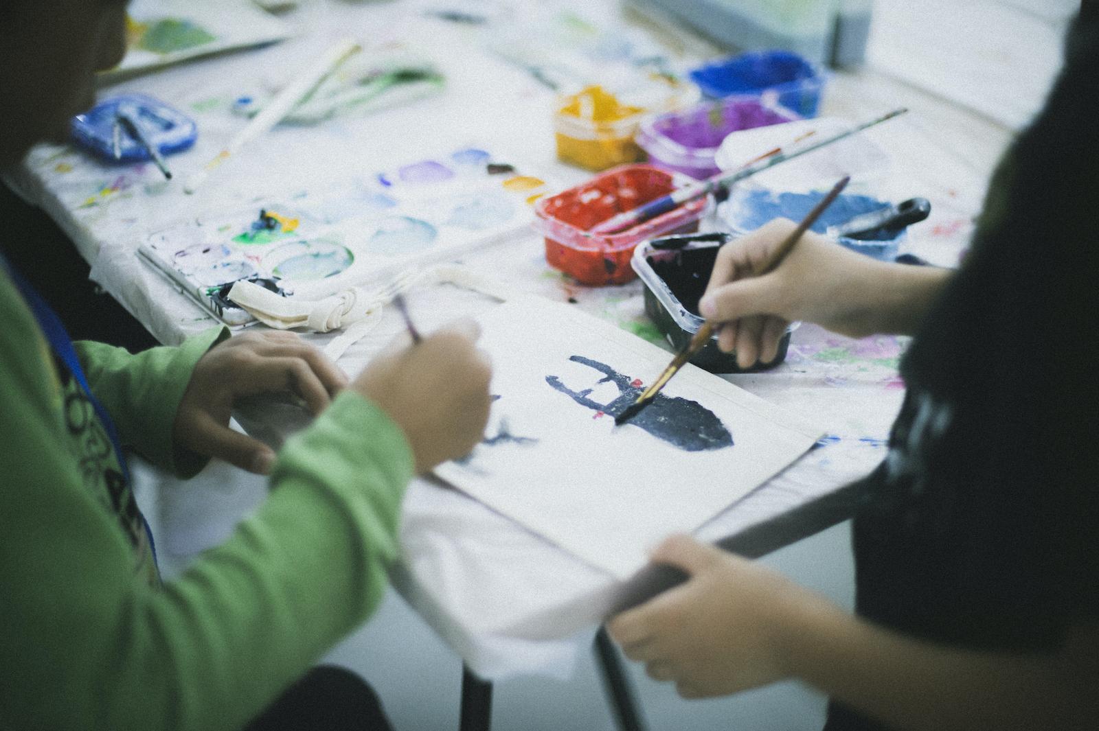 個展期間中に行われたワークショップの様子。子供たちがミニサコッシュに絵を描いている。