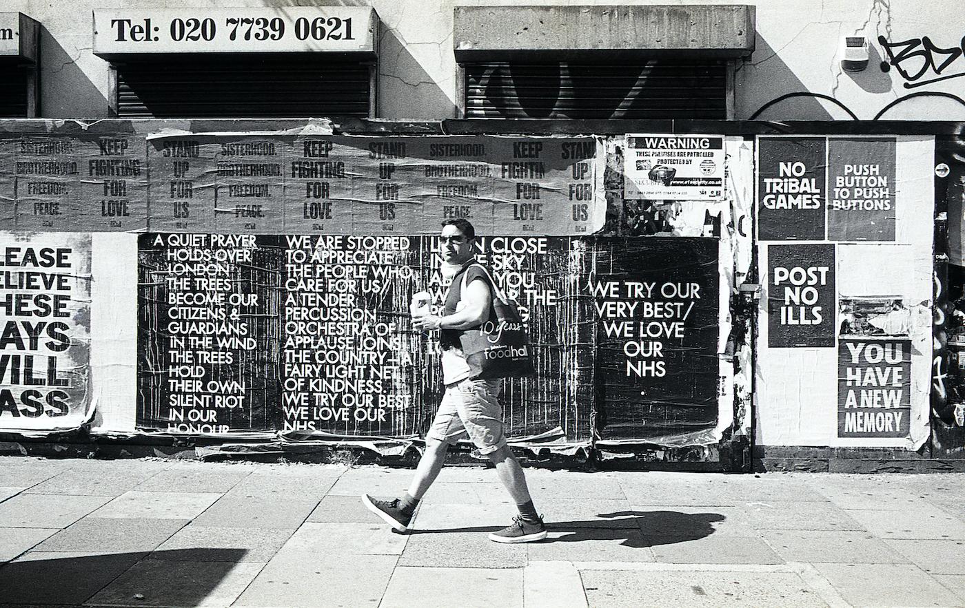 歩いてる人の後ろにはコロナによって起こったこの状況に対しての沢山のメッセージがポスターに書かれている。
