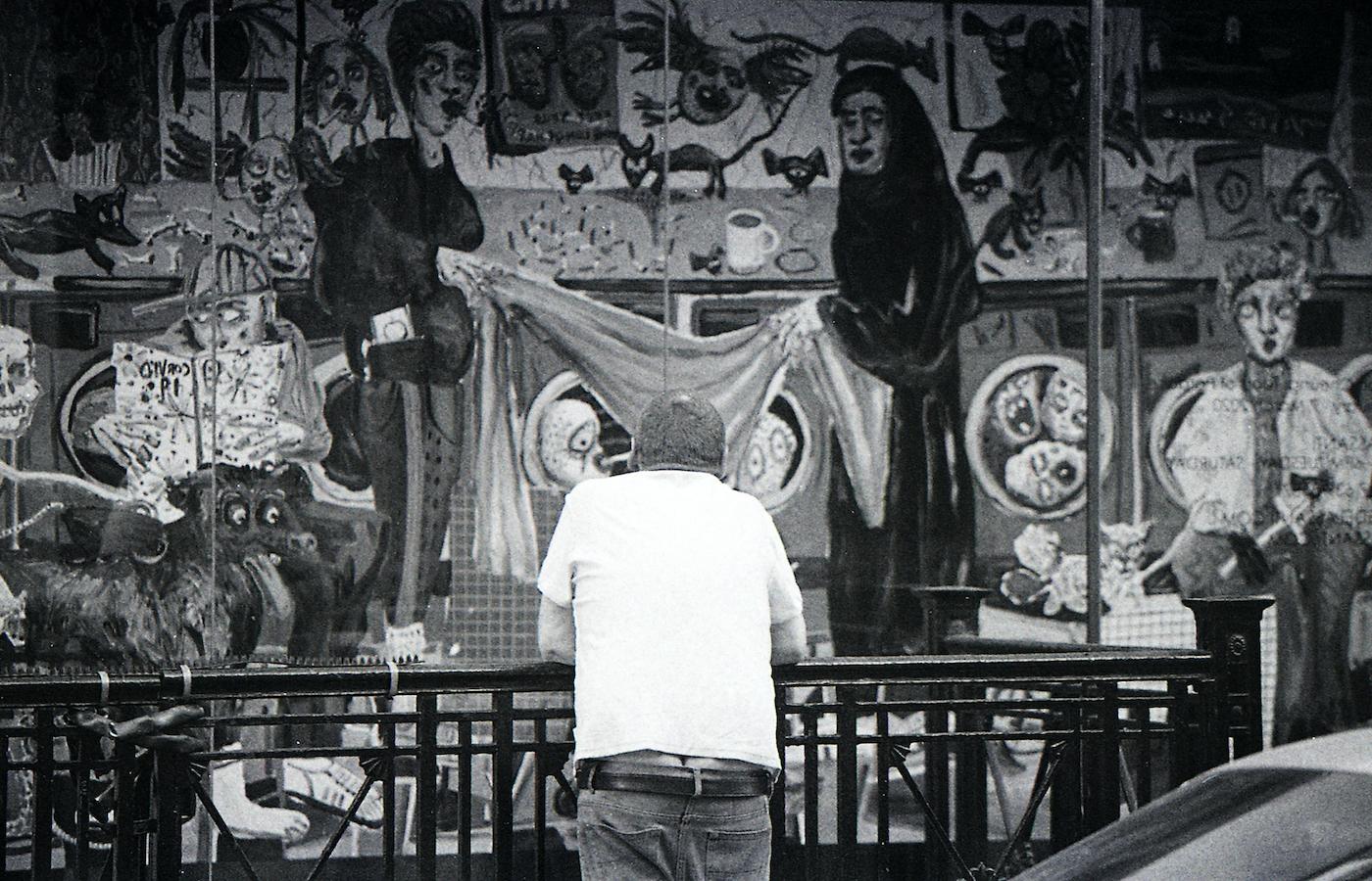 差別に対するメッセージがこもったストリートアートを眺める人。