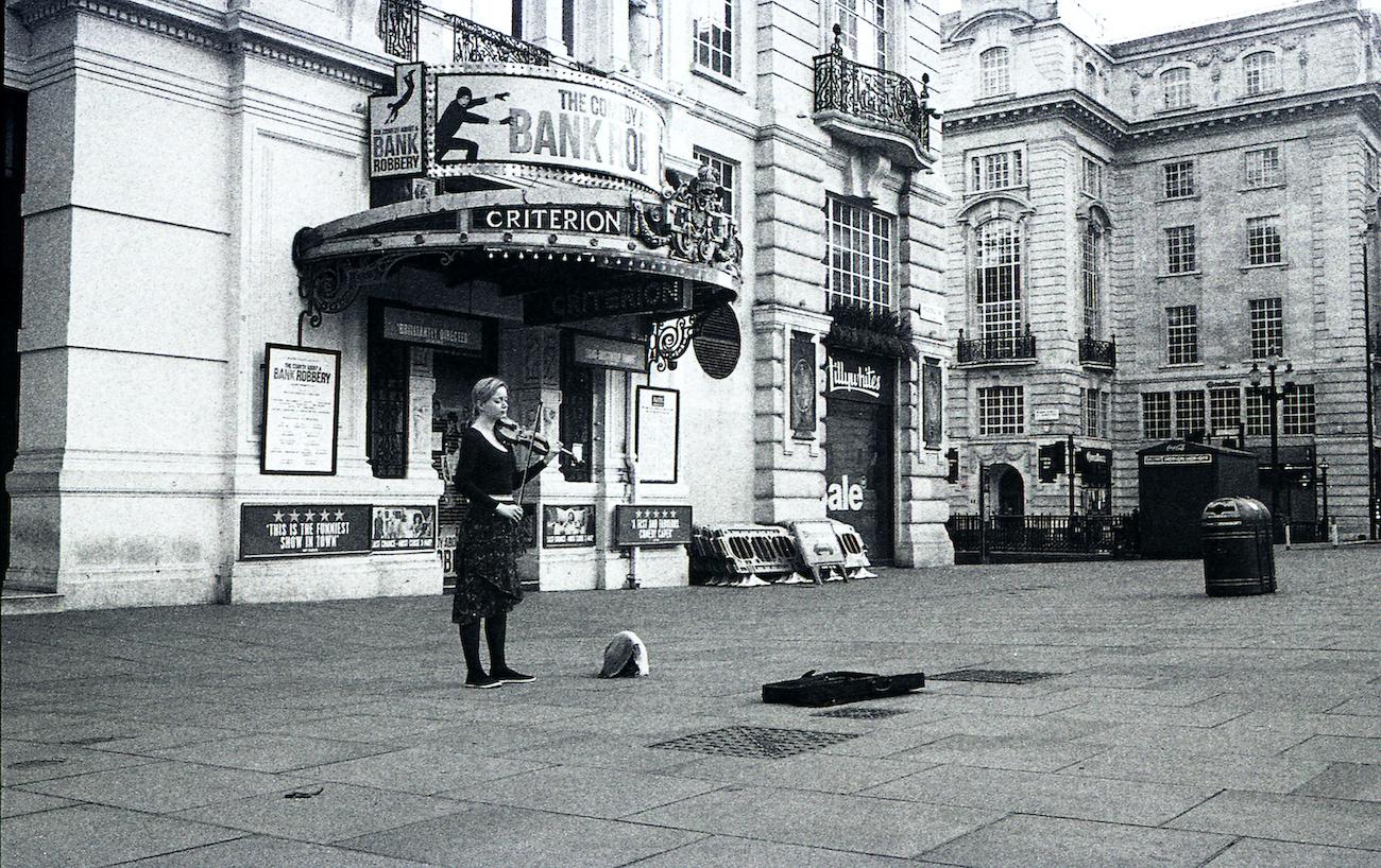 全く人がいない広場で演奏を続けるストリートミュージシャン。